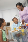 African American mother and children at breakfast — Stock Photo