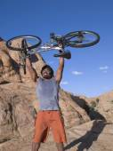 Man holding mountain bike over head — Stock Photo