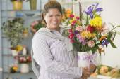 Hispanic woman holding flowers in vase — Stock Photo