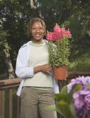 African American woman holding potted plant — Stock Photo