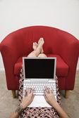 Tattooed Hispanic woman typing on laptop — Stock Photo