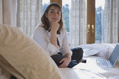 Hispanic woman sitting on bed next to laptop — Stock Photo