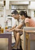 Multi-ethnic couple looking at laptop — Stock Photo