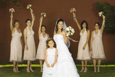 Hispanic bride and bridesmaids holding bouquets — Stock Photo