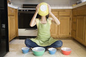 Asian woman with mixing bowls on floor — Stock Photo