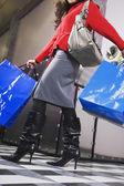 Hispanic woman carrying shopping bags — Stock Photo