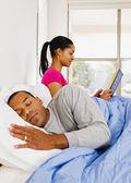 Woman reading next to sleeping husband — Stock Photo