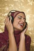 Middle Eastern woman listening to headphones — Stock Photo