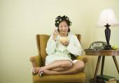 Asian woman in curlers eating cereal — Stock Photo