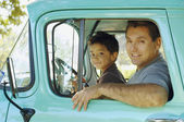 Hispanic father and son sitting in truck — Foto Stock
