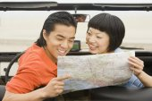 Asian couple looking at map — Stock Photo