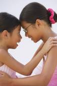 Asian sisters in ballet outfits hugging — Stock Photo