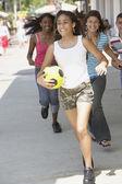 Multi-ethnic teenagers running on sidewalk — Stock Photo