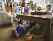 Children eating popcorn in livingroom — Stock Photo