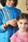 Indian grandmother fixing granddaughter's hair — Stock Photo