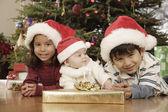 Hispanic siblings wearing Santa Claus hats — Stock Photo