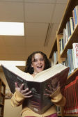 Girl holding library dictionary — Stock Photo