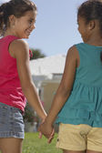 Mixed Race sisters holding hands — Stock Photo