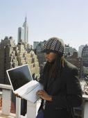African man looking at laptop in urban scene — Stock Photo