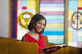 African American woman with Bible in church — Stock Photo