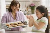 Hispanic mother and daughter with tray of cookies — Foto de Stock