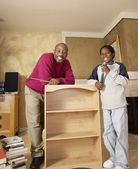 African father and son putting furniture together — Stock Photo