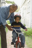 African grandfather teaching grandson to ride bicycle — Stock Photo