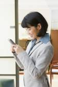 Asian businesswoman dialing cell phone — Stock Photo
