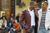 African men hugging with friends in background — Foto Stock