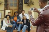 African man taking photograph of friends — Stock Photo