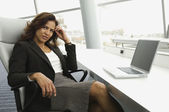 Hispanic businesswoman next to laptop — 图库照片