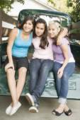 Hispanic teenaged girls sitting on truck tailgate — Stock Photo
