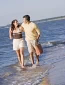 Hispanic couple walking in ocean surf — Stock Photo