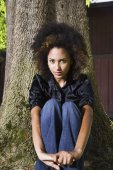 African woman sitting against tree — Stock Photo