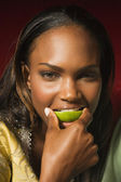 African woman biting lime slice — Stock Photo