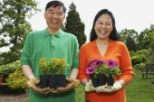 Senior Asian couple holding potted plants — Stock Photo