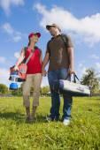 Hispanic couple carrying camping supplies — Stock Photo