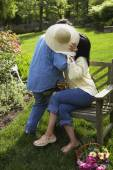 Hispanic couple hiding behind straw hat — Stockfoto