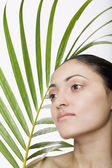 Indian woman next to palm frond — Stock Photo