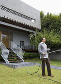 Man watering lawn in front of house — Stock Photo