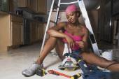 African woman on floor with power tools — Stock fotografie