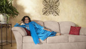 Indian woman sitting on sofa — Stock Photo