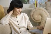 Asian woman looking at laptop — Stock Photo