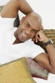 African American man laying on pillows — Stock Photo