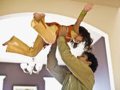 Indian father holding daughter in air — Stock Photo