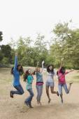 Hispanic teenaged girls cheering and jumping — Stock Photo