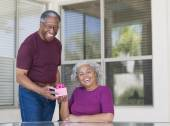 Senior African man giving gift to wife — Stock Photo