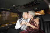 Well dressed senior couple kissing in limousine — Stock Photo