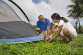 Multi-ethnic couple setting up tent — Stock Photo