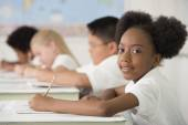 Children writing at desks in classroom — Stock Photo